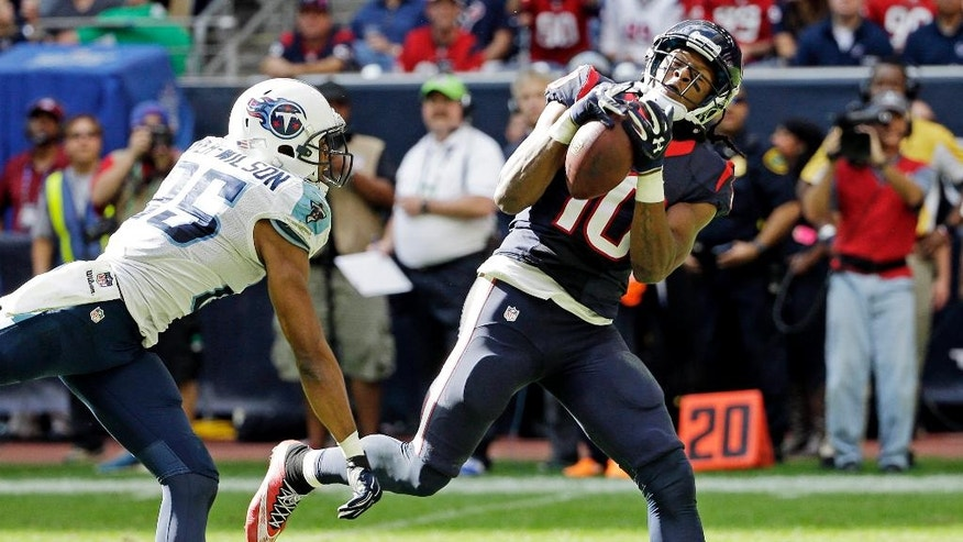 Houston Texans' DeAndre Hopkins catches a touchdown pass in front of Tennessee Titans' Blidi Wreh-Wilson during the first half of an NFL football game Sunday, Nov. 30, 2014, in Houston. (AP Photo/David J. Phillip)