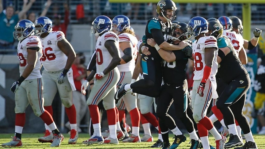 Jacksonville Jaguars kicker Josh Scobee, center, gets a hug from teammate long snapper Carson Tinker after kicking a 43-yard field goal to defeat the New York Giants 25-24 in an NFL football game in Jacksonville, Fla., Sunday, Nov. 30, 2014. (AP Photo/John Raoux)