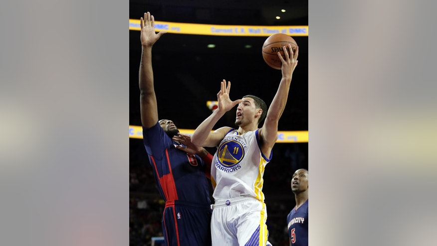 Golden State Warriors' Klay Thompson (11) takes a shot against Detroit Pistons' Andre Drummond (0) during the first half of an NBA basketball game Sunday, Nov. 30, 2014, in Auburn Hills, Mich. (AP Photo/Duane Burleson)