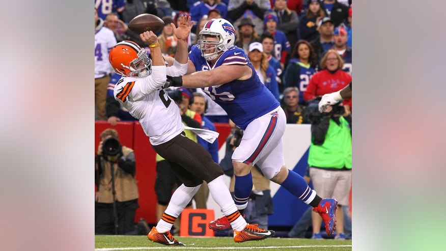Cleveland Browns quarterback Johnny Manziel, left, loses the ball as Buffalo Bills defensive tackle Kyle Williams applies pressure during the second half of an NFL football game, Sunday, Nov. 30, 2014, in Orchard Park, N.Y. The play was ruled a forward pass. (AP Photo/Bill Wippert)