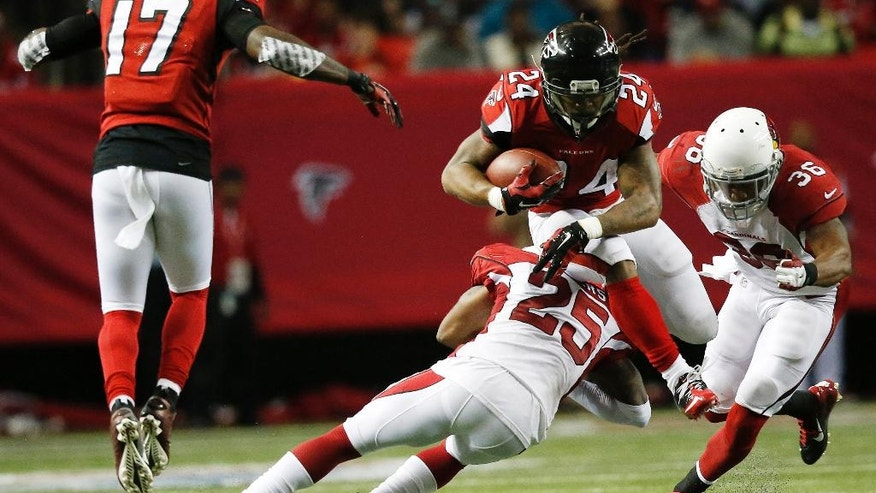 Atlanta Falcons running back Devonta Freeman (24) leaps over Arizona Cardinals cornerback Jerraud Powers (25) during the first half of an NFL football game, Sunday, Nov. 30, 2014, in Atlanta. (AP Photo/Brynn Anderson )