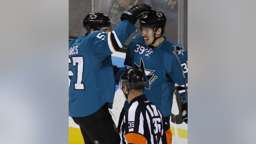 San Jose Sharks' Logan Couture, right, celebrates with Tommy Wingels after scoring a goal against the Anaheim Ducks during the first period of an NHL hockey game, Saturday, Nov. 29, 2014, in San Jose, Calif. (AP Photo/George Nikitin)