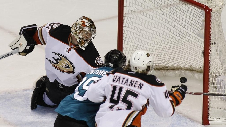 San Jose Sharks' Logan Couture, center, scores past Anaheim Ducks goalie Frederik Anderson during the first period of an NHL hockey game, Saturday, Nov. 29, 2014, in San Jose, Calif. At right is Ducks' Sami Vatanen. (AP Photo/George Nikitin)