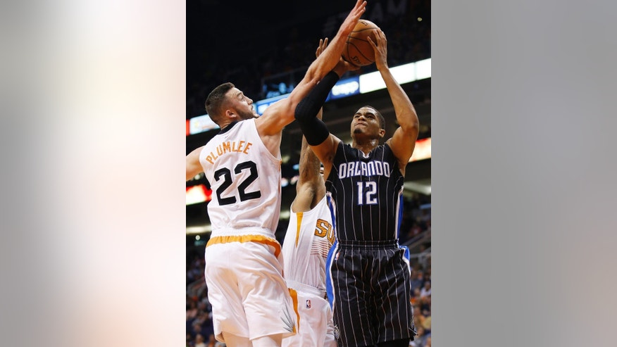 Phoenix Suns' Miles Plumlee (22) blocks the shot of Orlando Magic's Tobias Harris (12) during the first half of an NBA basketball game Sunday, Nov. 30, 2014, in Phoenix. (AP Photo/Ross D. Franklin)
