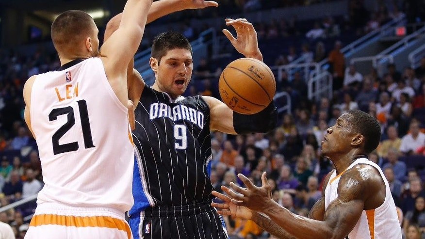 Orlando Magic's Nikola Vucevic (9), of Montenegro, is fouled by Phoenix Suns' Eric Bledsoe, right, as Suns' Alex Len (21), of Ukraine, defends during the first half of an NBA basketball game Sunday, Nov. 30, 2014, in Phoenix. (AP Photo/Ross D. Franklin)