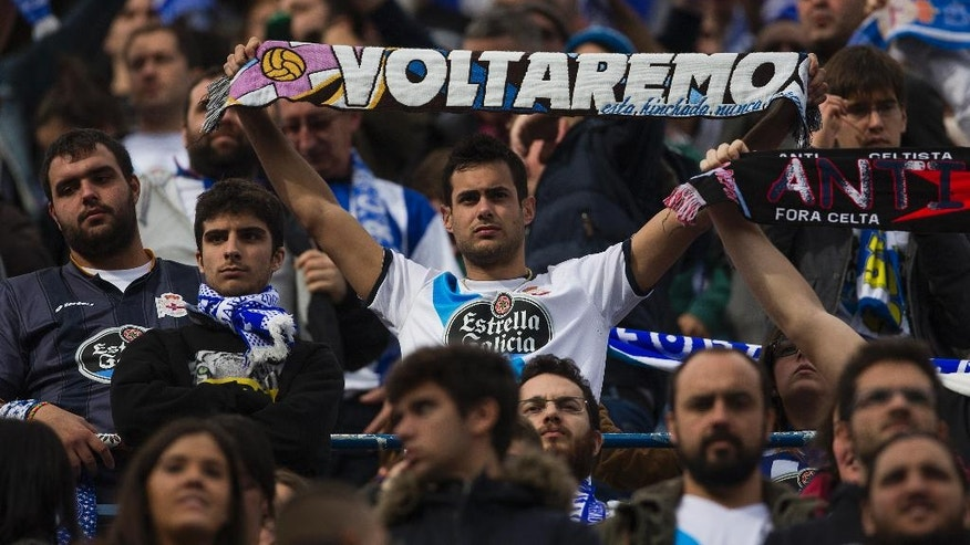 "Coruna's fan displays a scarf reading ""We will come back"" during a Spanish La Liga soccer match between Atletico and Deportivo Coruna at the Vicente Calderon stadium in Madrid, Spain, Sunday, Nov. 30, 2014. Officials said a man was hospitalized in critical condition, eleven others suffered minor injuries and two were arrested after a fight broke out outside Atletico Madrid's football stadium between its fans and those of Deportivo La Coruna on Sunday. Madrid emergency service SAMUR and police said the clash between the rival fans broke out at 0800 GMT near the Vicente Calderon stadium. One man with head injuries had to be rescued from the nearby Manzanares River. The man, identified only as a 43-year-old Deportivo fan, was resuscitated and taken to Madrid's Clinico hospital. (AP Photo/Andres Kudacki)"