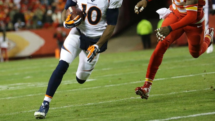 Denver Broncos wide receiver Emmanuel Sanders (10) runs away from Kansas City Chiefs free safety Husain Abdullah (39) in the first half of an NFL football game in Kansas City, Mo., Sunday, Nov. 30, 2014. (AP Photo/Charlie Riedel)