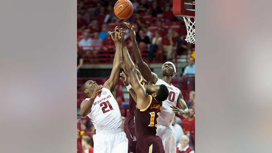 Arkansas' Manuale Watkins (21) and Bobby Portis (10) reach up for the rebound with Iona's David Laury (13) in the first half of an NCAA college basketball game in Fayetteville, Ark., Sunday, Nov. 30, 2014. (AP Photo/Sarah Bentham)