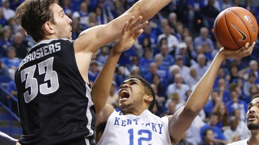 Kentucky's Karl-Anthony Towns (12) shoots under pressure from Providence's Carson Desrosiers (33) during the first half of an NCAA college basketball game, Sunday, Nov. 30, 2014, in Lexington, Ky. (AP Photo/James Crisp)