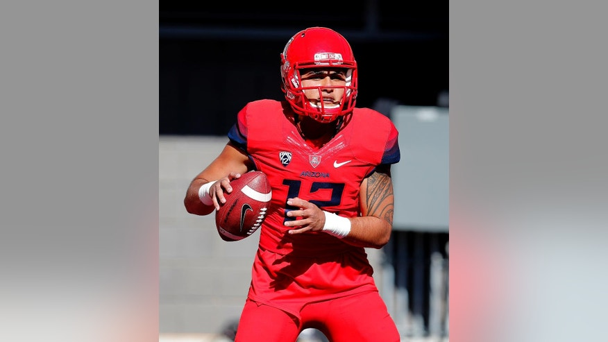 Arizona quarterback Anu Solomon (12) warms up before an NCAA college football game against Arizona State, Friday, Nov. 28, 2014, in Tucson, Ariz. (AP Photo/Rick Scuteri)