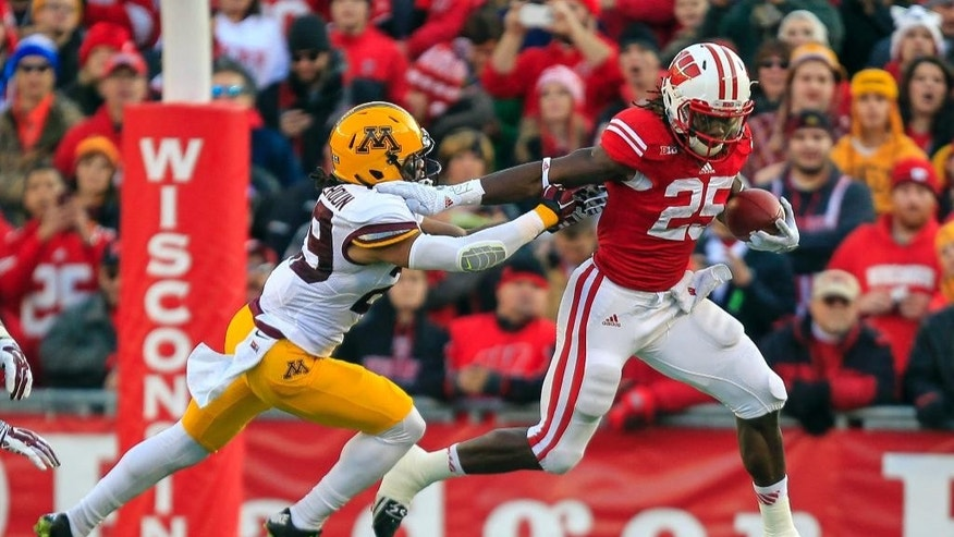 Wisconsin's Melvin Gordon (25) runs against Minnesota's Brien Boddy-Calhoun during the first half of an NCAA college football game Saturday, Nov. 29, 2014, in Madison, Wis. (AP Photo/Andy Manis)