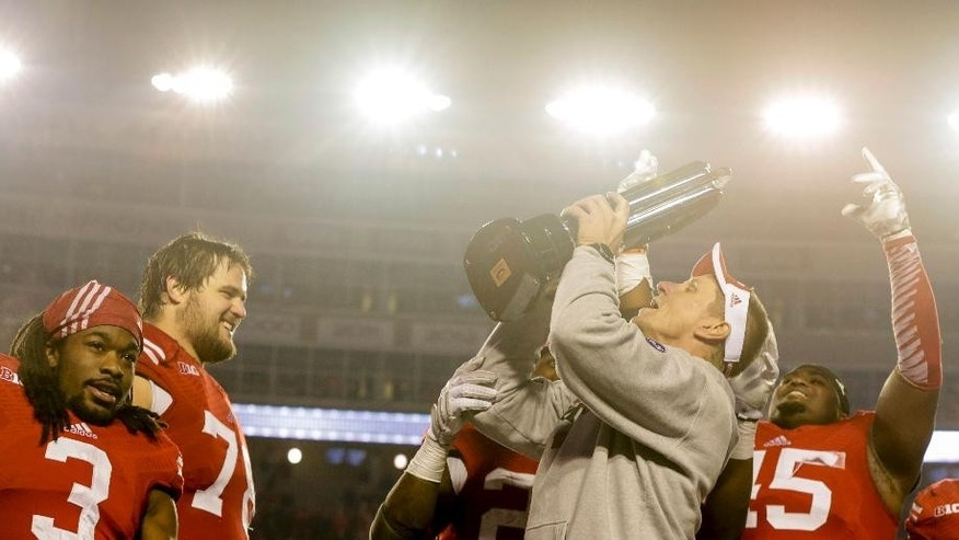 Wisconsin coach Gary Andersen celebrates with the Big 10 Western Divisional Trophy after Wisconsin beat Minnesota 34-24 in an NCAA college football game Saturday, Nov. 29, 2014, in Madison, Wis. (AP Photo/Andy Manis)