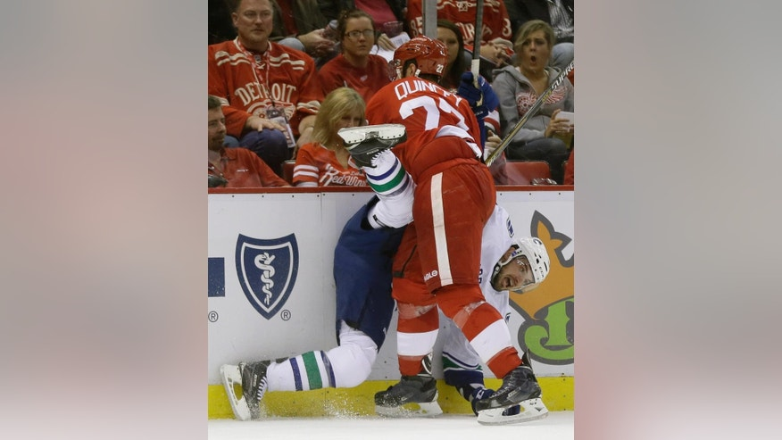 Detroit Red Wings defenseman Kyle Quincey (27) checks Vancouver Canucks center Brad Richardson (15) during the first period of an NHL hockey game in Detroit, Sunday, Nov. 30, 2014. (AP Photo/Carlos Osorio)
