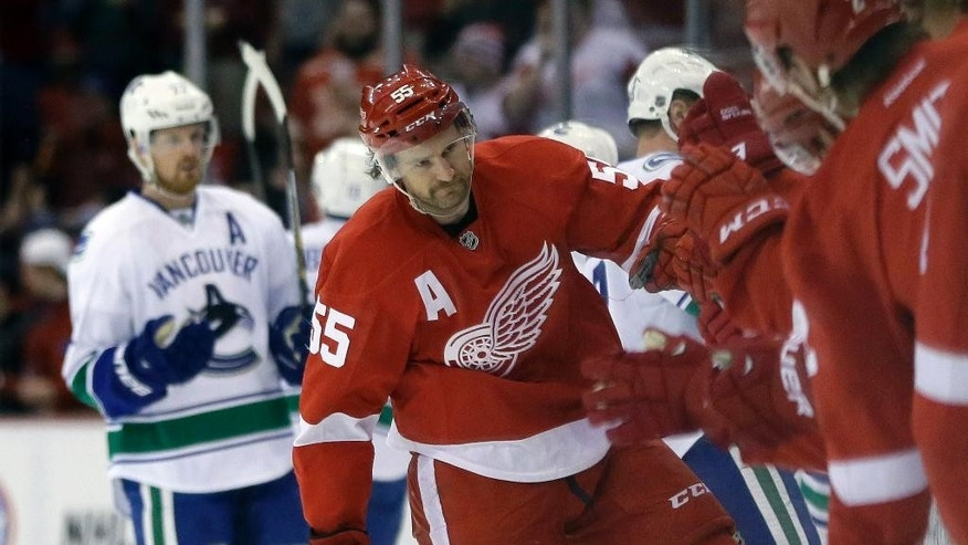 Detroit Red Wings defenseman Niklas Kronwall (55) is congratulated by teammates after his goal during the first period of an NHL hockey game against the Vancouver Canucks in Detroit, Sunday, Nov. 30, 2014. (AP Photo/Carlos Osorio)