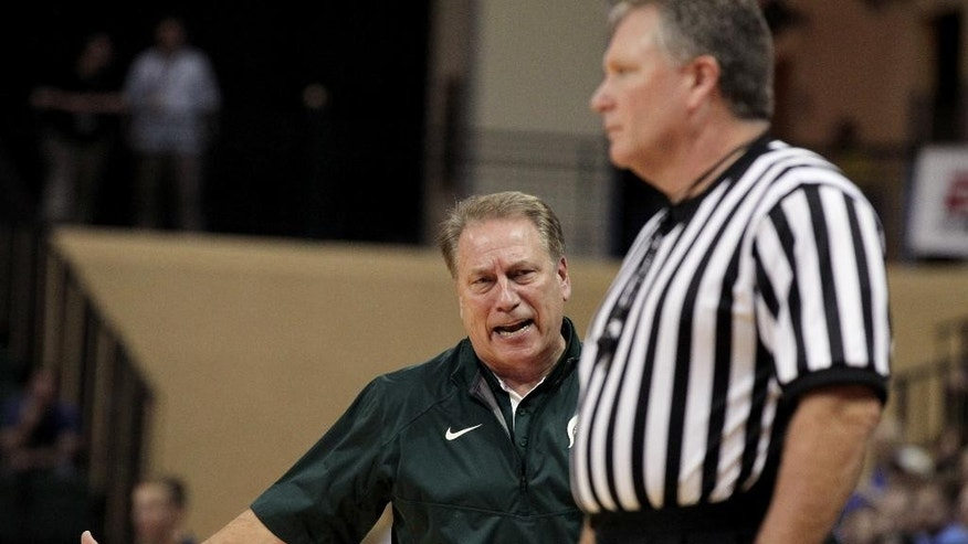 Michigan State head coach Tom Izzo, left, talks to referee Karl Hess during the second half of an NCAA college basketball game in Lake Buena Vista, Fla., Sunday, Nov. 30, 2014. Kansas won 61-56. (AP Photo/Reinhold Matay)