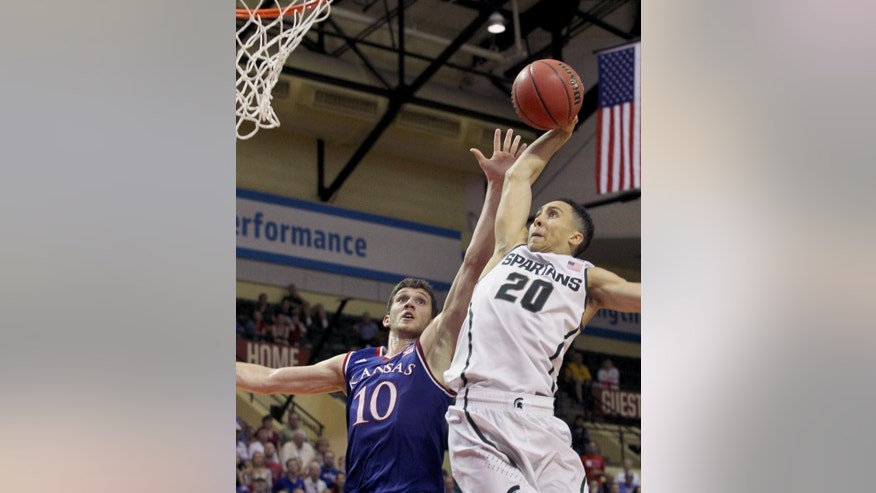 Michigan State guard Travis Trice (20) shoots past Kansas guard Sviatoslav Mykhailiuk (10) during the second half of an NCAA college basketball game in Lake Buena Vista, Fla., Sunday, Nov. 30, 2014. Kansas won 61-56. (AP Photo/Reinhold Matay)