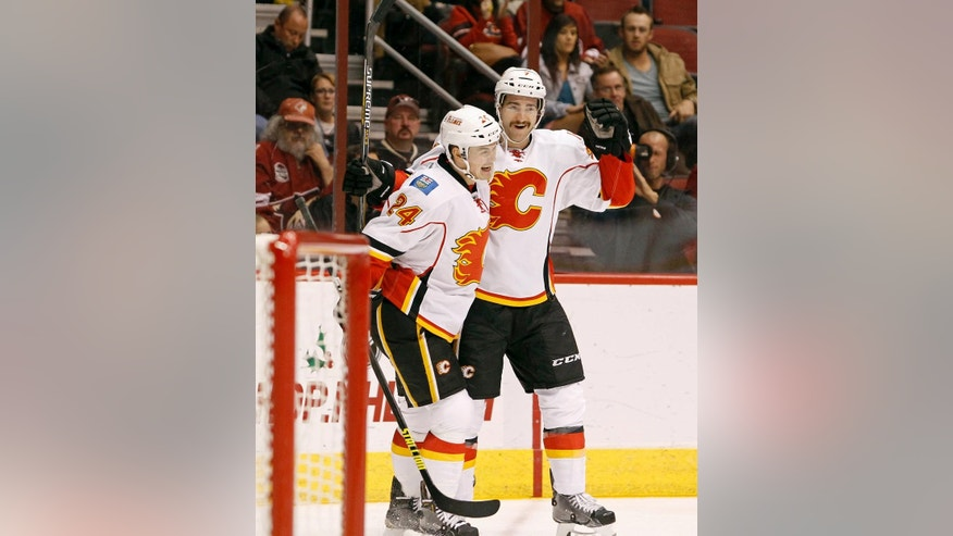 Calgary Flames' Jiri Hudler (24), of the Czech Republic, and T.J. Brodie celebrate Brodie's second period goal against the Arizona Coyotes during an NHL game Saturday, Nov. 29, 2014 in Glendale, Ariz. (AP Photo/Ralph Freso)