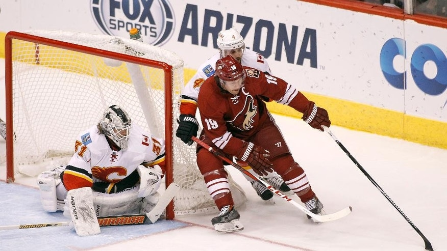 Arizona Coyotes' Shane Doan (19) works the puck in on Calgary Flames goaltender Karri Ramo (31), of Finland, as Calgary's Kris Russell (4) defends during the first period of an NHL game Saturday, Nov. 29, 2014 in Glendale, Ariz. (AP Photo/Ralph Freso)