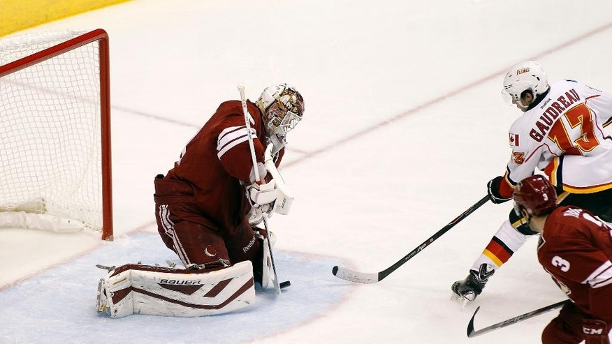 Arizona Coyotes goaltender Devan Dubnyk, left, makes a save on the shot by Calgary Flames' Johnny Gaudreau (13) as Coyotes' Keith Yandle (3) defends  during the first period of an NHL game Saturday, Nov. 29, 2014 in Glendale, Ariz. (AP Photo/Ralph Freso)