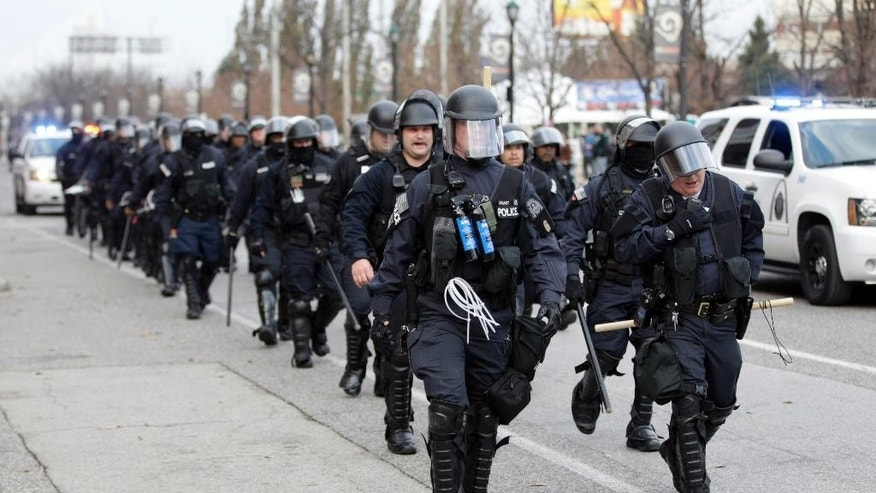 Police wearing riot gear walk past Edward Jones Dome following an NFL football game between the St. Louis Rams and the Oakland Raiders, Sunday, Nov. 30, 2014, in St. Louis. Police and protesters clashed after the game as protests continue following a grand jury's decision not to indict a Ferguson police officer in the shooting death of Michael Brown. (AP Photo/Tom Gannam)