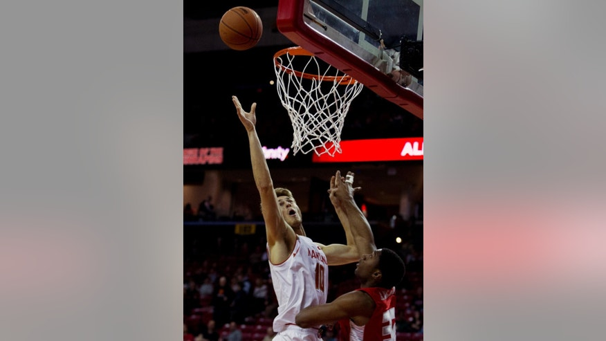Maryland's Jake Layman (10) shoots to the basket as VMI's Phillip Anglade (32) defends during the first half of an NCAA college basketball game in College Park, Md., Sunday, Nov. 30, 2014. (AP Photo/Jose Luis Magana)