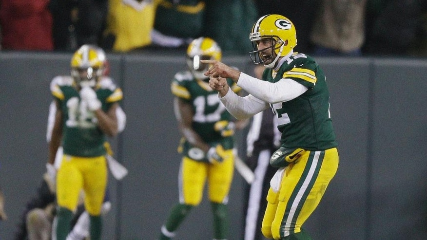 Green Bay Packers quarterback Aaron Rodgers celebrates a 45-yard touchdown pass to Jordy Nelson during the first half of an NFL football game against the New England Patriots Sunday, Nov. 30, 2014, in Green Bay, Wis. (AP Photo/Tom Lynn)