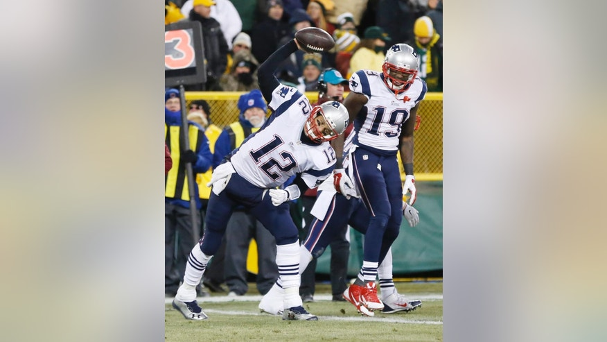 New England Patriots' Tom Brady spikes the ball after throwing a touchdown pass to Brandon LaFell (19) during the first half of an NFL football game against the Green Bay Packers Sunday, Nov. 30, 2014, in Green Bay, Wis. (AP Photo/Tom Lynn)