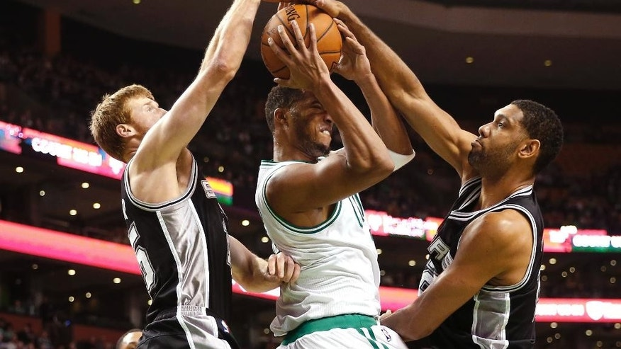 San Antonio Spurs' Tim Duncan, right, and Matt Bonner combine to stop Boston Celtics' Evan Turner during the first quarter of an NBA basketball game in Boston, Sunday, Nov. 30, 2014. (AP Photo/Winslow Townson)