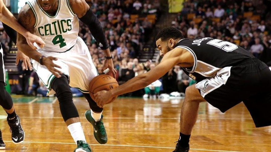 Boston Celtics' Marcus Thornton (4) has the ball stripped away by San Antonio Spurs' Cory Joseph during the first quarter of an NBA basketball game in Boston, Sunday, Nov. 30, 2014. (AP Photo/Winslow Townson)