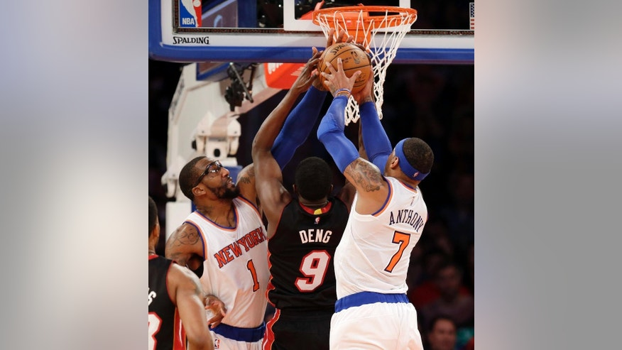 Miami Heat's Luol Deng, center, fights with New York Knicks' Amar'e Stoudemire, left, and Carmelo Anthony for a rebound during the first half of an NBA basketball game, Sunday, Nov. 30, 2014, in New York. (AP Photo/Seth Wenig)
