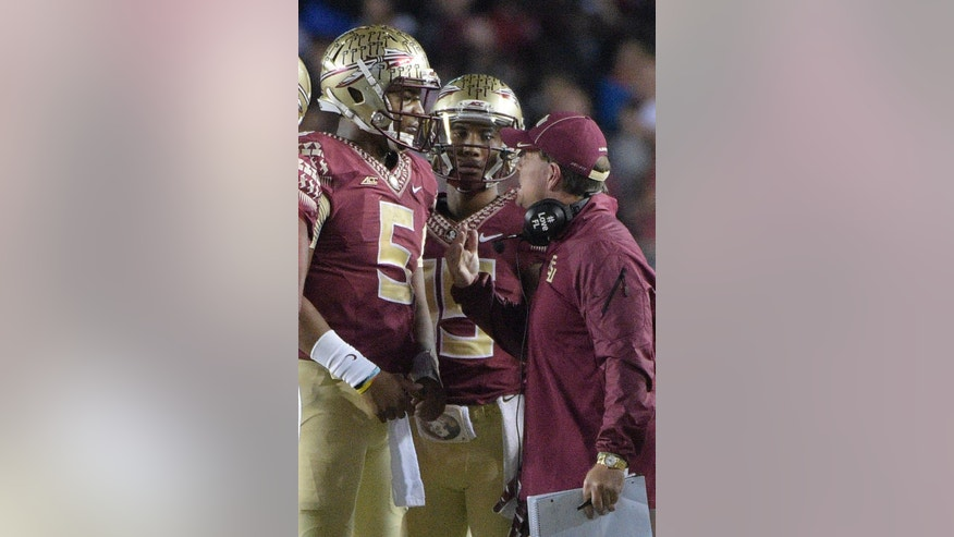 Florida State head coach Jimbo Fisher, right, talks to quarterback Jameis Winston (5) during a timeout in the second half of an NCAA college football game against Florida in Tallahassee, Fla., Saturday, Nov. 29, 2014. Florida State won 24-19.(AP Photo/Phelan M. Ebenhack)