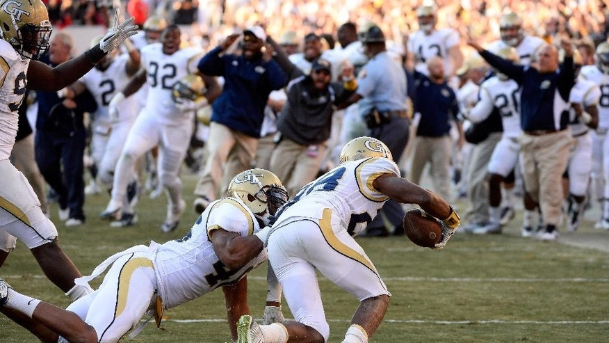 The Georgia Tech bench reacts after defensive back D.J. White (28) intercepted a pass from Georgia quarterback Hutson Mason to seal a 30-24 overtime win in an NCAA college football game Saturday, Nov. 29, 2014, in Athens, Ga. (AP Photo/David Tulis)