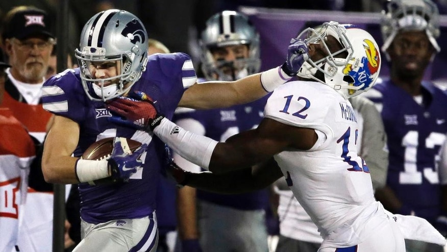 Kansas State wide receiver Curry Sexton, left, stiff arms Kansas cornerback Dexter McDonald (12) during the second half of an NCAA college football game in Manhattan, Kan., Saturday, Nov. 29, 2014. Kansas State won 51-13. (AP Photo/Orlin Wagner)