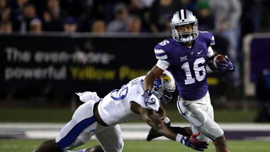 Kansas State kick returner Tyler Lockett (16) escapes a tackle by Kansas special teams player Justin McCay (19) during the second half of an NCAA college football game in Manhattan, Kan., Saturday, Nov. 29, 2014. Kansas State won 51-13. (AP Photo/Orlin Wagner)