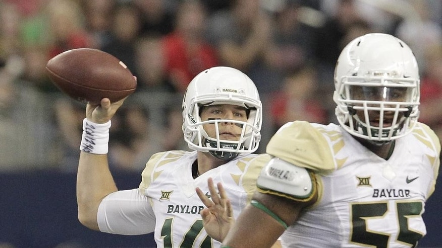 Baylor quarterback Bryce Petty (14) drops back to pass while offensive lineman Kyle Fuller gives protection in the first half of an NCAA college football game against Texas Tech, Saturday, Nov. 29, 2014, in Arlington, Texas. (AP Photo/Tim Sharp)