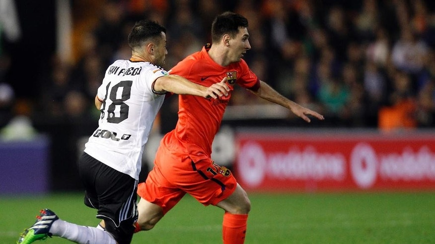 Barcelona's Lionel Messi, from Argentina, right, drives the ball with Valencia's Javi Fuego  during a Spanish La Liga soccer match at the Mestalla stadium in Valencia, Spain, on Sunday, Nov. 30, 2014.(AP Photo/Alberto Saiz)