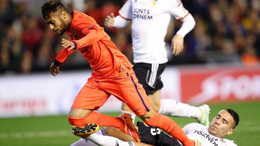Barcelona's Neymar, left, from Brazil, is tackled by Valencia's Daniel Parejo during a Spanish La Liga soccer match at the Mestalla stadium in Valencia, Spain, on Sunday, Nov. 30, 2014.(AP Photo/Alberto Saiz)