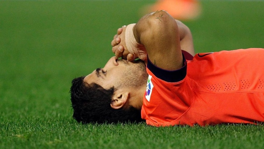 Barcelona's Luis Suarez, from Uruguay, reacts after failing to score against Valencia during a Spanish La Liga soccer match at the Mestalla stadium in Valencia, Spain, on Sunday, Nov. 30, 2014.(AP Photo/Alberto Saiz)