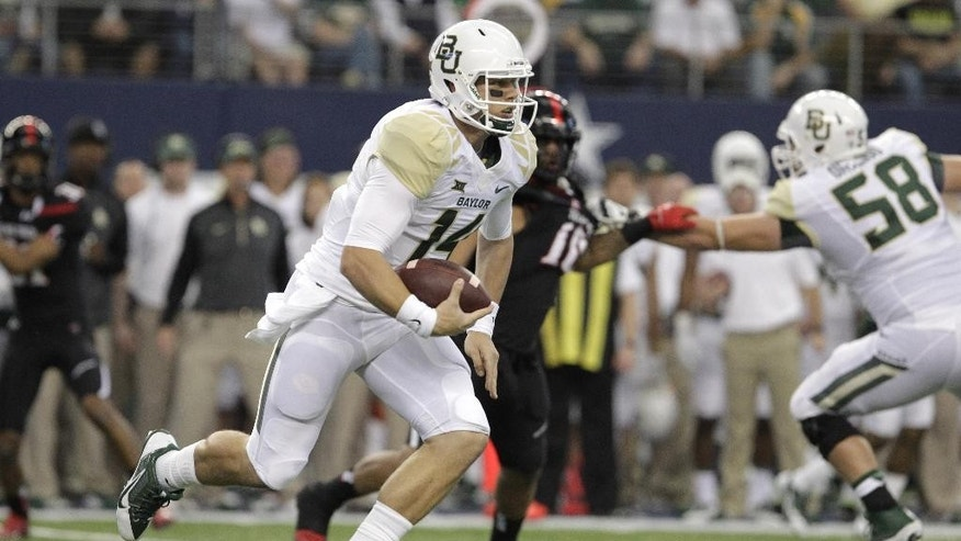 Baylor quarterback Bryce Petty (14) carries the ball against Texas Tech in the first half of an NCAA college football game, Saturday, Nov. 29, 2014, in Arlington, Texas.  Baylor won the game 48-46. (AP Photo/Tim Sharp)