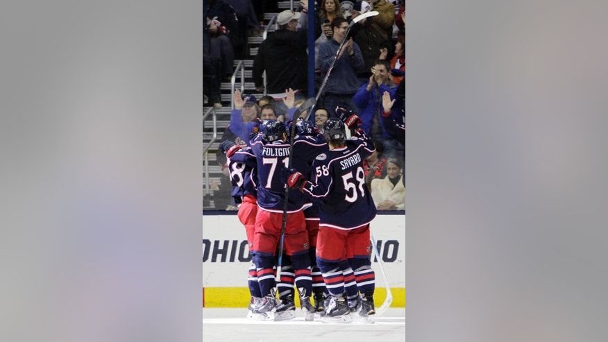 Columbus Blue Jackets players celebrate the game-winning goal against the Florida Panthers during the third period of an NHL hockey game Monday, Dec. 1, 2014, in Columbus, Ohio. The Blue Jackets won 2-1. (AP Photo/Jay LaPrete)