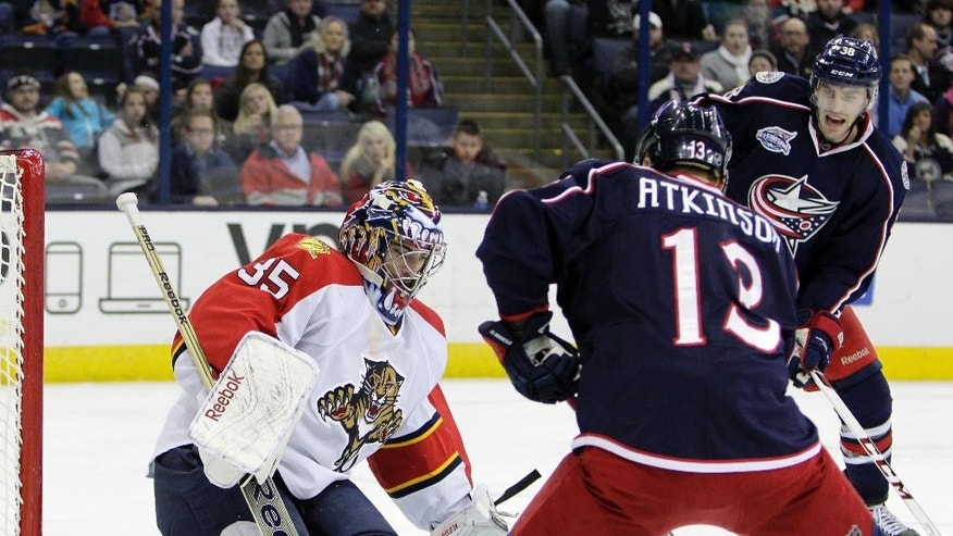Florida Panthers' Al Montoya, left, makes a save against Columbus Blue Jackets' Boone Jenner, right, and Cam Atkinson during the second period of an NHL hockey game Monday, Dec. 1, 2014, in Columbus, Ohio. (AP Photo/Jay LaPrete)