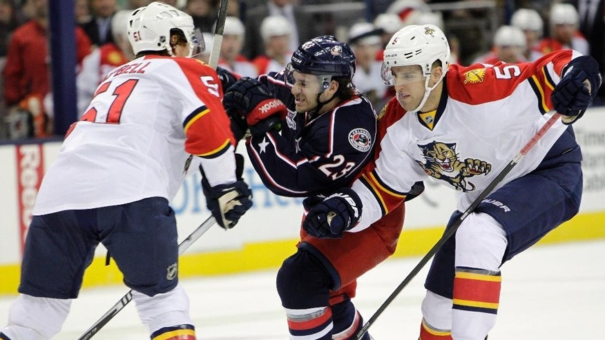 Columbus Blue Jackets' Brian Gibbons, center, tries to skate between Florida Panthers' Brian Campbell, left, and Aaron Ekblad during the second period of an NHL hockey game Monday, Dec. 1, 2014, in Columbus, Ohio. (AP Photo/Jay LaPrete)