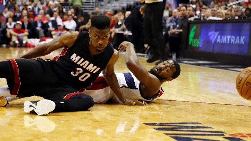 Miami Heat guard Norris Cole (30) and Washington Wizards guard John Wall keep their eyes on the loose ball in the second half of an NBA basketball game, Monday, Dec. 1, 2014, in Washington. The Wizards won 107-86. (AP Photo/Alex Brandon)