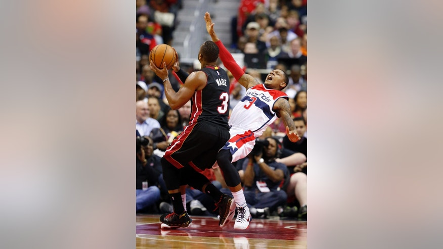 Washington Wizards guard Bradley Beal, right, draws a charging foul on Miami Heat guard Dwyane Wade in the second half of an NBA basketball game, Monday, Dec. 1, 2014, in Washington. The Wizards won 107-86. (AP Photo/Alex Brandon)