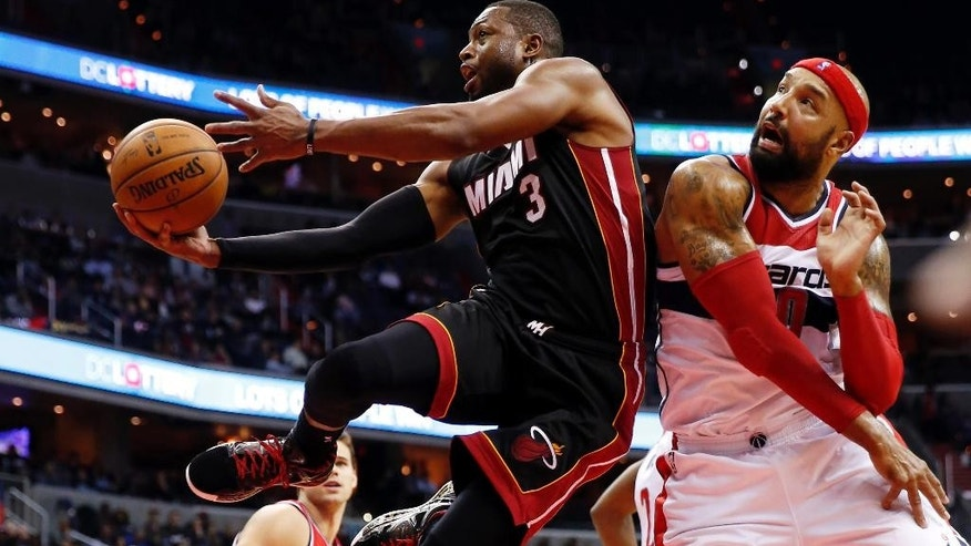 Miami Heat guard Dwyane Wade (3) shoots as he drives past Washington Wizards forward Drew Gooden (90) in the first half of an NBA basketball game, Monday, Dec. 1, 2014, in Washington. (AP Photo/Alex Brandon)
