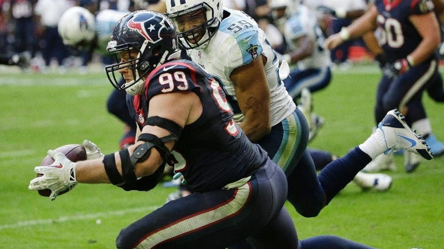 Houston Texans' J.J. Watt catches a touchdown pass in front of Tennessee Titans' Wesley Woodyard (59) during the second half of an NFL football game Sunday, Nov. 30, 2014, in Houston. (AP Photo/David J. Phillip)