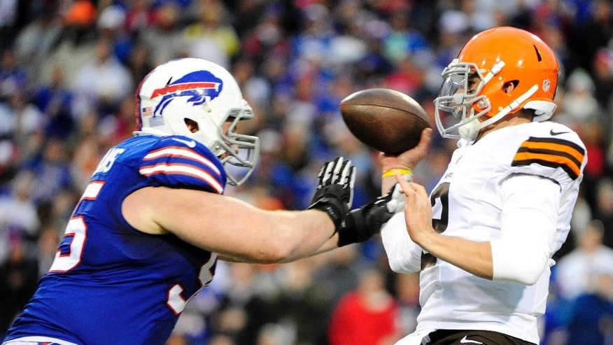 El quarterback Johnny Manziel de los Browns de Cleveland, derecha, pierde el balón ante el asedio del defensive tackle Kyle Williams de los Bills de Buffalo, el domingo 30 de noviembre de 2014. (AP Foto/Gary Wiepert)