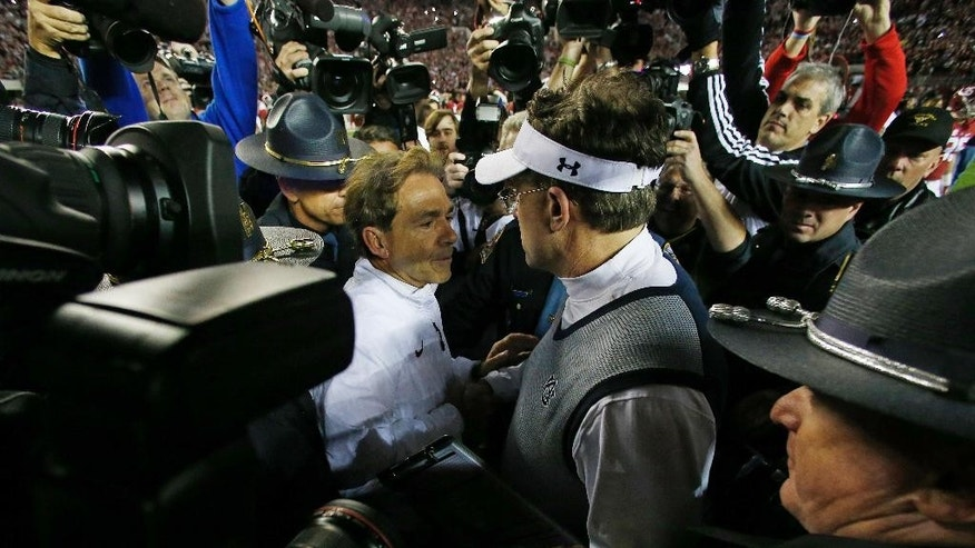 Alabama head coach Nick Saban, left, speaks with Auburn head coach Gus Malzahn after the second half of the Iron Bowl NCAA college football game, Saturday, Nov. 29, 2014, in Tuscaloosa, Ala. Alabama won 55-44. (AP Photo/Butch Dill)