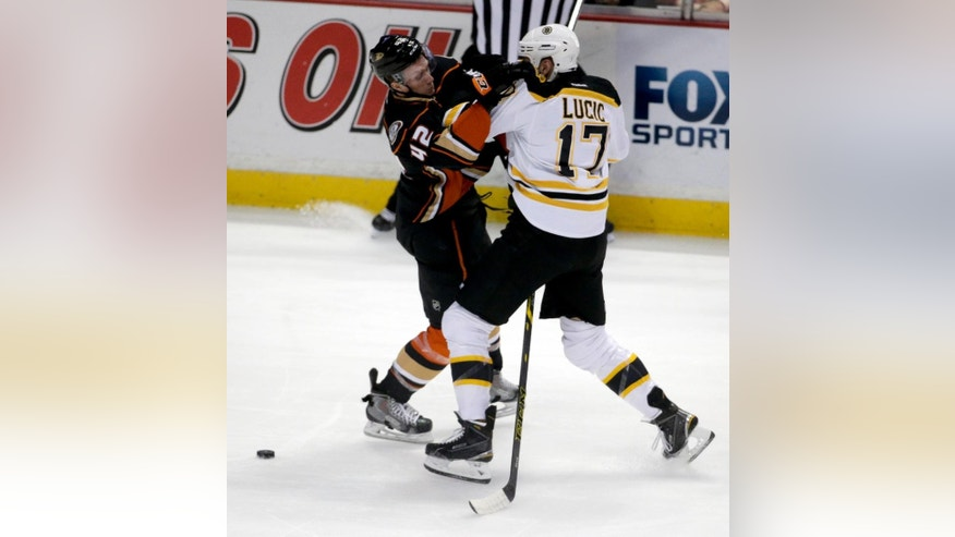 Anaheim Ducks defenseman Josh Manson, left, collides with Boston Bruins left wing Milan Lucic during the first period of an NHL hockey game in Anaheim, Calif., Monday, Dec. 1, 2014. (AP Photo/Chris Carlson)
