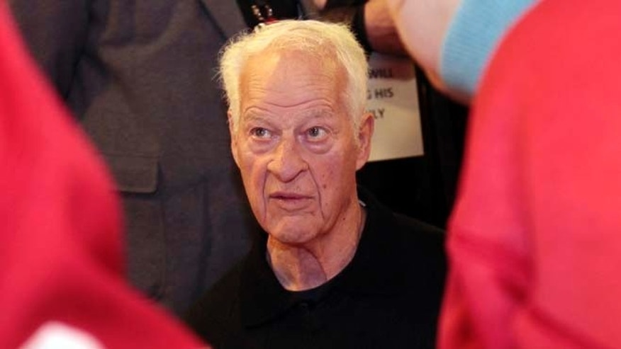 March 31, 2013: Former Detroit Red Wings player Gordie Howe signs autographs for fans in celebration of his 85th birthday before the start of the Red Wing's NHL hockey game against the Chicago Blackhawks in Detroit, Michigan.